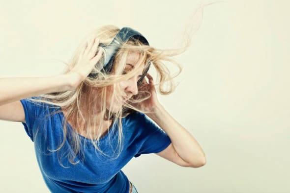 young woman singing with headphones on a light background