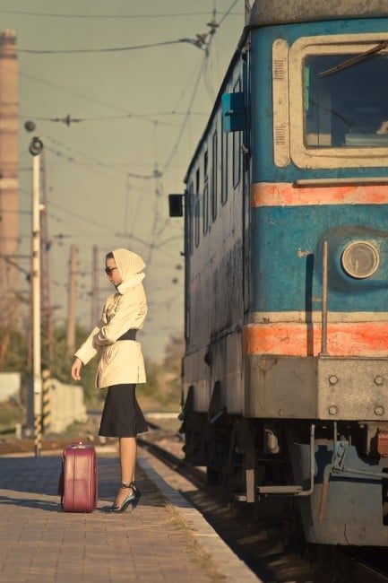 Woman in sunglasses waiting train on railroad station. The autumn cold weather. Beige coat. Retro suitcase.