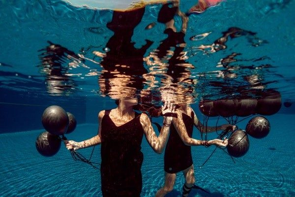Two Women Underwater Black Balloons